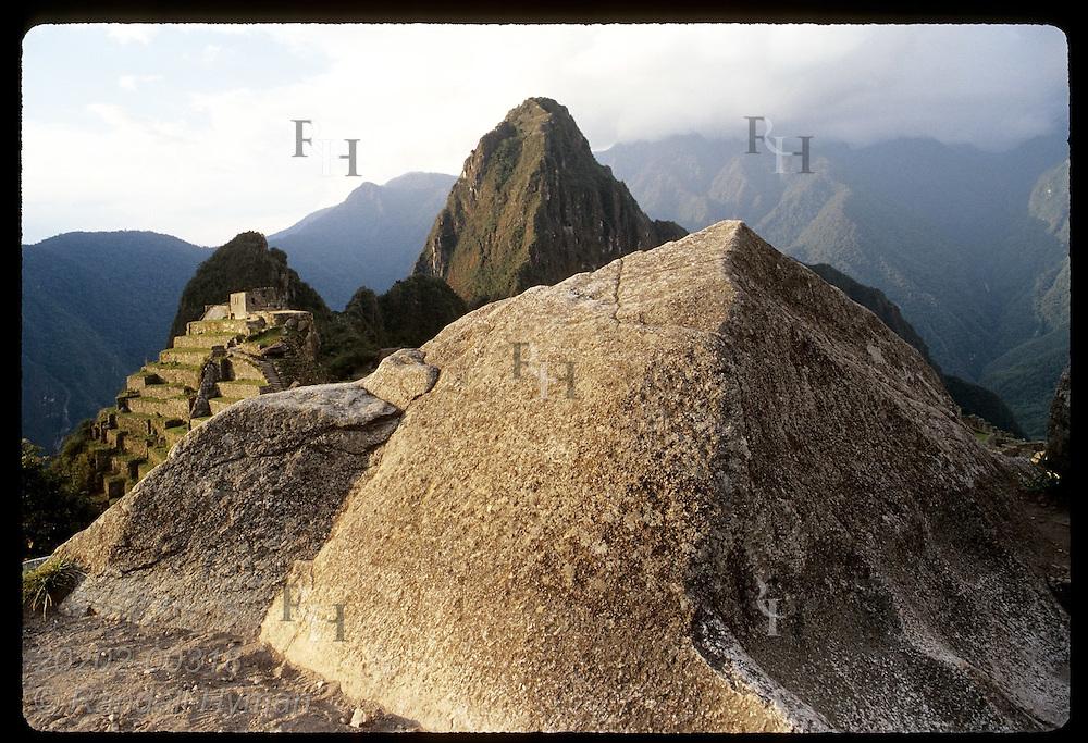 Carved rock mimics sacred peak Huayna Picchu framing Intihuatana and Sacred Plaza; Machu Picchu. Peru
