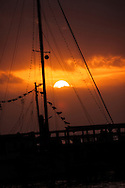 A silhouetted sailboat at sunset, along the Mississippi Gulf Coast. Photo shot in Biloxi.