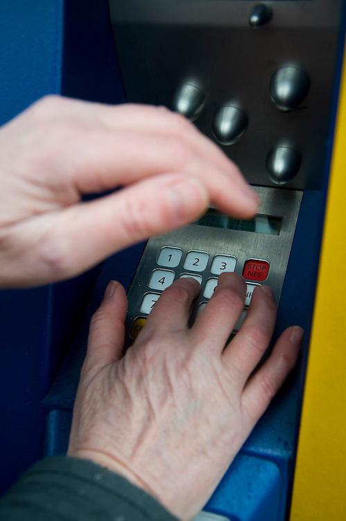 Nederland, Driebergen, 19 feb 2009.Met de ene hand je pincode intoetsen, met de andere hand voorkomen dat met een boven het toetsenbord geplaatst cameraatje je pincode wordt gefilmd..Foto (c) Michiel Wijnbergh