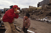 Central America, Honduras, Tegucigalpa. Devastation in the aftermath of Hurricane Mitch. High winds and flooding. Refugees. Street Children roaming the streets, addicted and sniffing glue. Infrastructure destroyed.