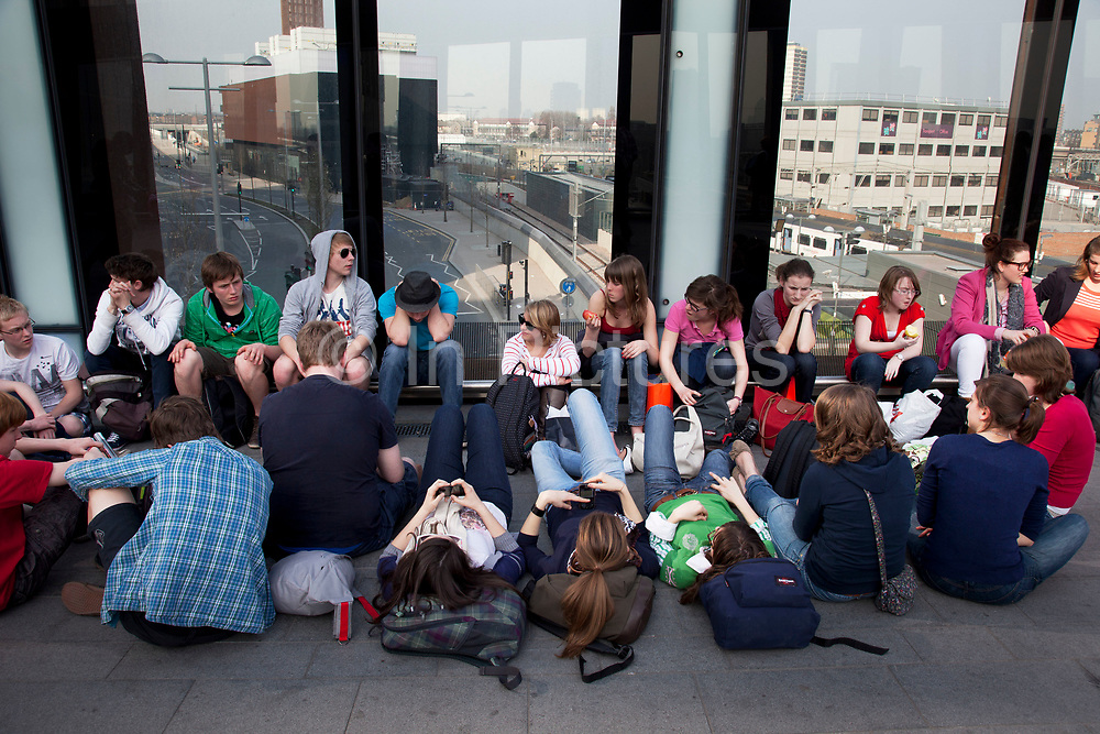 Scene of students hanging out outside as people flock away from the old Stratford shopping centre towards the new Westfield Shoppping Centre in Stratford, East London, UK. This is Europe's largest shopping complex. This is a relatively poor area of London, but in recent years has seen much regeneration, the construction of a major transport hub and various shopping complexes. Stratford is adjacent to the London Olympic Park and is currently experiencing regeneration and expansion linked to the 2012 Summer Olympics.