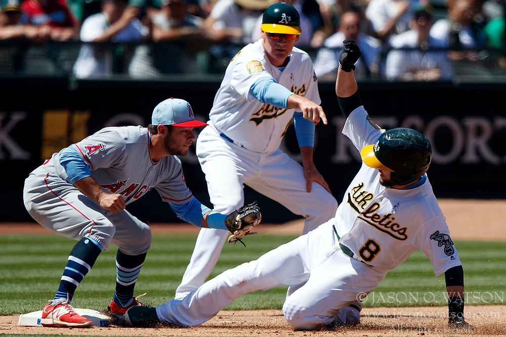 OAKLAND, CA - JUNE 17:  Jed Lowrie #8 of the Oakland Athletics slides into third base ahead of a tag from David Fletcher #6 of the Los Angeles Angels of Anaheim in front of third base coach Matt Williams #4 during the seventh inning at the Oakland Coliseum on June 17, 2018 in Oakland, California. The Oakland Athletics defeated the Los Angeles Angels of Anaheim 6-5 in 11 innings. (Photo by Jason O. Watson/Getty Images) *** Local Caption *** Jed Lowrie; David Fletcher; Matt Williams