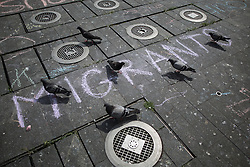 "© Licensed to London News Pictures . 23/05/2015 . Manchester , UK . Pigeons walk across "" MIGRANTS "" chalking on disused fountains in Manchester's Piccadilly Gardens . A demonstration , organised by "" The People's Assembly "" , against austerity in Piccadilly Gardens in Central Manchester , attended by approximately 2000 people . Photo credit : Joel Goodman/LNP"