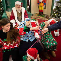 VINELAND, NJ:  (L-R) Erin Derieux, 13, Nicholas Leary, 13, Mason, 7,<br /> and  Emily, 10, remote their face masks before taking photos with Santa Claus at the Cumberland Mall in Vineland, NJ on December 6, 2020. Warburg was a maintenance man at the 88 year old shopping destination for 15 years before staring to depict Santa Claus 5 years ago.  The pandemic has forced difficult decisions about maintaining the holiday tradition of visits to Santa Claus versus safety concerns.  Plexiglass dividers, face shields, and physical distancing are among the precautions for those locations that have proceeded with Santa photo opportunities.  CREDIT:  Mark Makela for The New York Times