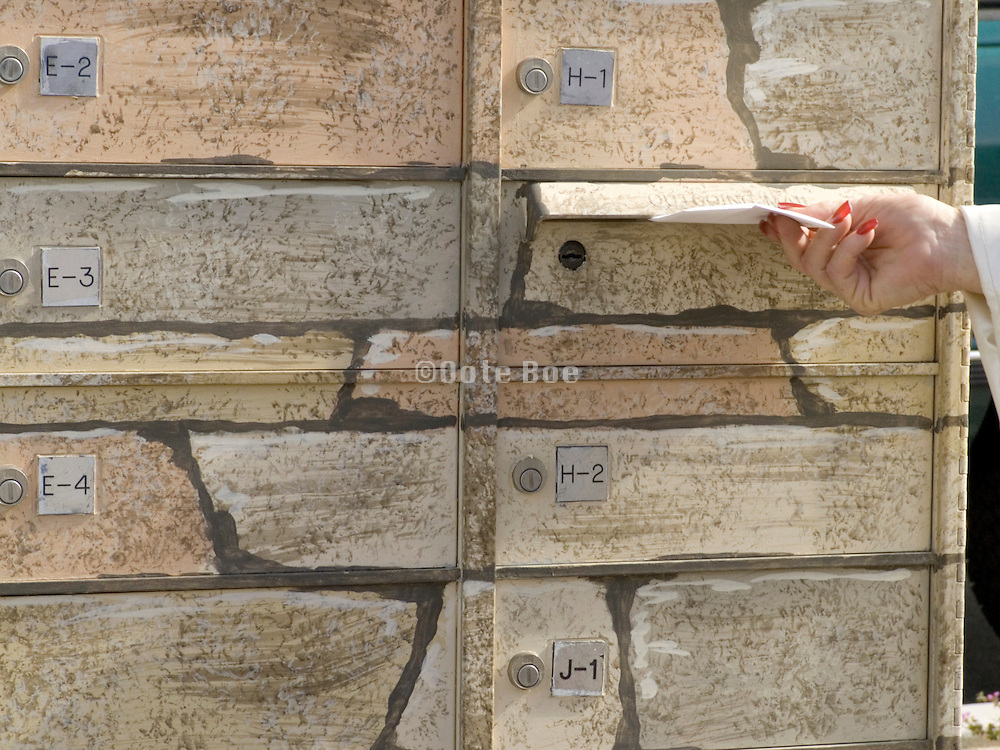 stone pattern designed mailbox with female hand dropping a letter in the mail