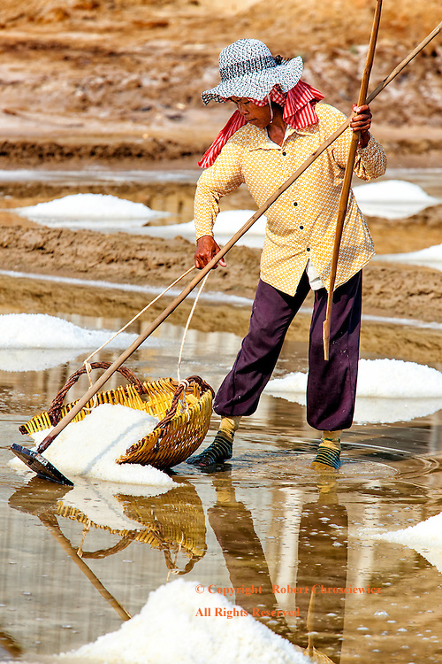 Salt: A shoeless woman collects the raked salt so it may be stored away , Kampot Cambodia.