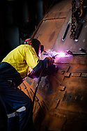 A welder works on part of an iron ore haulage truck at a mine site in the Pilbara region of Western Australia.
