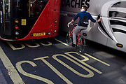 An urban cyclist leans against a tour coach in central London. The rider on his bike is taking his life in his own hands by wishing to squeeze between the large vehicles on this busy street in the capital. So far in 2015, 15 people have been killed on the capital's roads, most of them women.