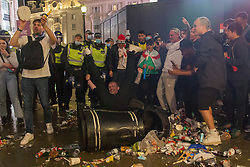 © Licensed to London News Pictures.  12/07/2021. London, UK. England football supporters smash the bin in Piccadilly Circus, central London as England lose to Italy on penalties during the EURO 2020. Photo credit: Marcin Nowak/LNP