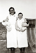 two nurses posing with newborn babies England 1930s