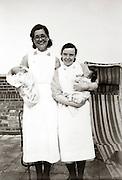 two nurses posing with newborn babies England 1930s