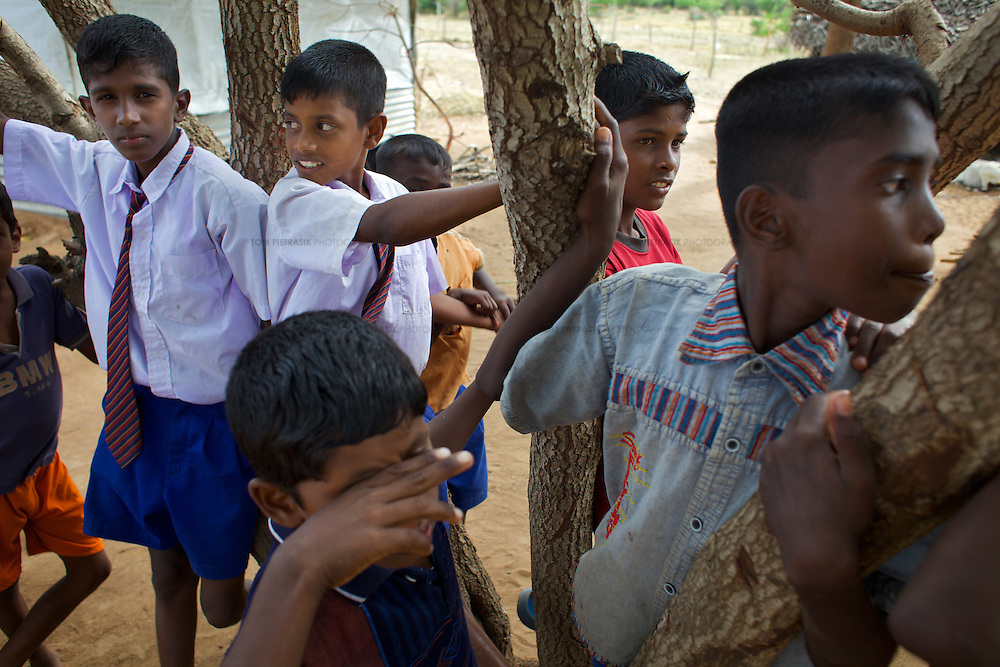 Brothers M. Siranjeevithan, 13 (left), and M. Chandrakumar, 11 (both in school uniform) outside a the home of a neighbour. <br /> <br /> Brothers M. Siranjeevithan, 13, and M. Chandrakumar, 11, attend Vadamunai Government Tamil Mixed School. Their father was killed, an innocent bystander in the conflict between the LTTE and Sri Lankan Government 11 years ago. The brothers' mother cares for them though they must both fish to supplement the family income. M. Siranjeevithan and M. Chandrakumar live with their mother in one of a dozen temporary makeshift shelters housing conflict-displaced Tamil families located 3km from the Vadamunai Government Tamil Mixed School.<br /> <br /> After fighting between the LTTE and Colombo Government forced displacement of the local Tamil community, the Vadamunai Government Tamil Mixed School was closed in 2007. Since reopening in January 2009, the school has six teaching staff for 88 pupils. Before closure, 136 pupils studied at the school. Five classes are held in a Unicef supplied Temporary Learning Space. Four other classes are conducted outside. Many of the students suffer with the trauma and stress associated with those living in conflict situations. The staff must deal with these issues as well as the personal difficulties that they also themselves suffer living in a conflict environment. <br /> <br /> Photo: Tom Pietrasik<br /> Batticaloa District, Sri Lanka<br /> September 30th 2009