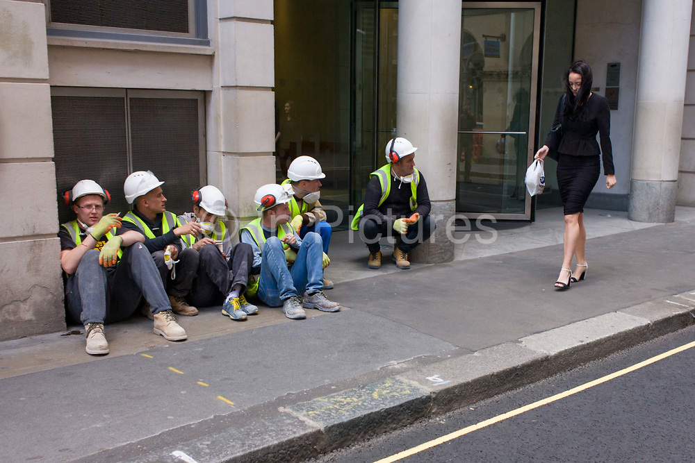 Workmen from a nearby construction site, admire a lone, young woman walking past in a City of London street. The lady looks uneasily down so as not to maintain eye contact on the men eager to eye her up and down in a moment of sexist attention accepted by the working man. The woman may be well-educated and successful with a good job and intelligent friends while the men are pleased to spend their lunchtime admiring the opposite sex.