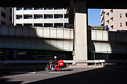 A postman for japan Post (Japanese post office) rides a deliver motorbike under expressway overpasses in Sangenjaya, Tokyo, Japan. Thursday November 21st 2019