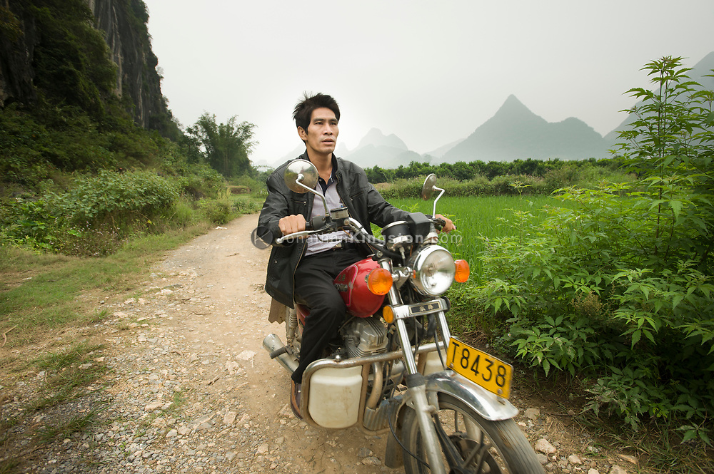 A man riding a motorcycle on a dirt road near Yangshuo, China.