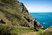 Woman enjoying a healthy active lifestyle jogging and exploring the north coast cliff paths in Jersey, Channel Islands on a sunny day in Spring