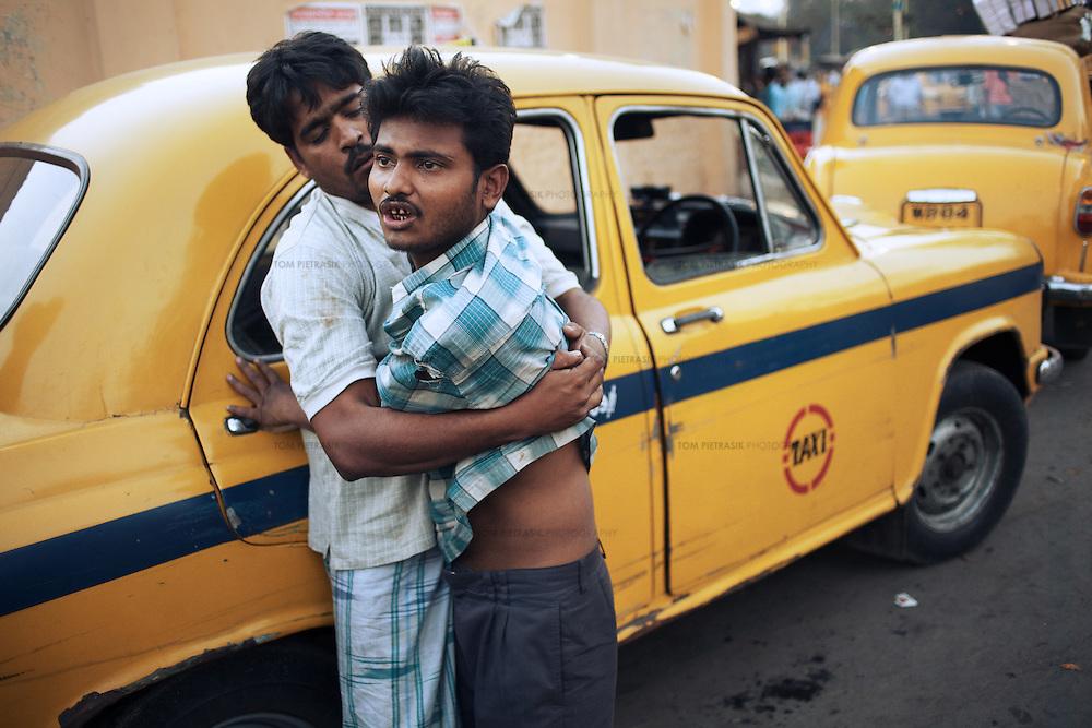 Men involved in a drunken dispute on the streets of Kolkata. The The yellow Ambassador taxi is still ubiquitous in Kolkata...Photo: Tom Pietrasik.Kolkata, West Bengal. India.February 17th 2009