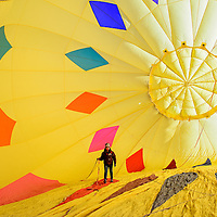120613       Cable Hoover<br /> <br /> Pilot Katelyn Salazar retrieves a rope from the interior of her balloon as it inflates during the Red Rock Balloon Rally at Red Rock Park in Gallup Friday. No balloons launched but Salazar said she hoped the static inflation would help satisfy the crowd.