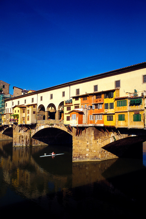 A scull (rowboat) passes under the Ponte Vecchio (bridge) along the River Arno in the center of Florence, Italy