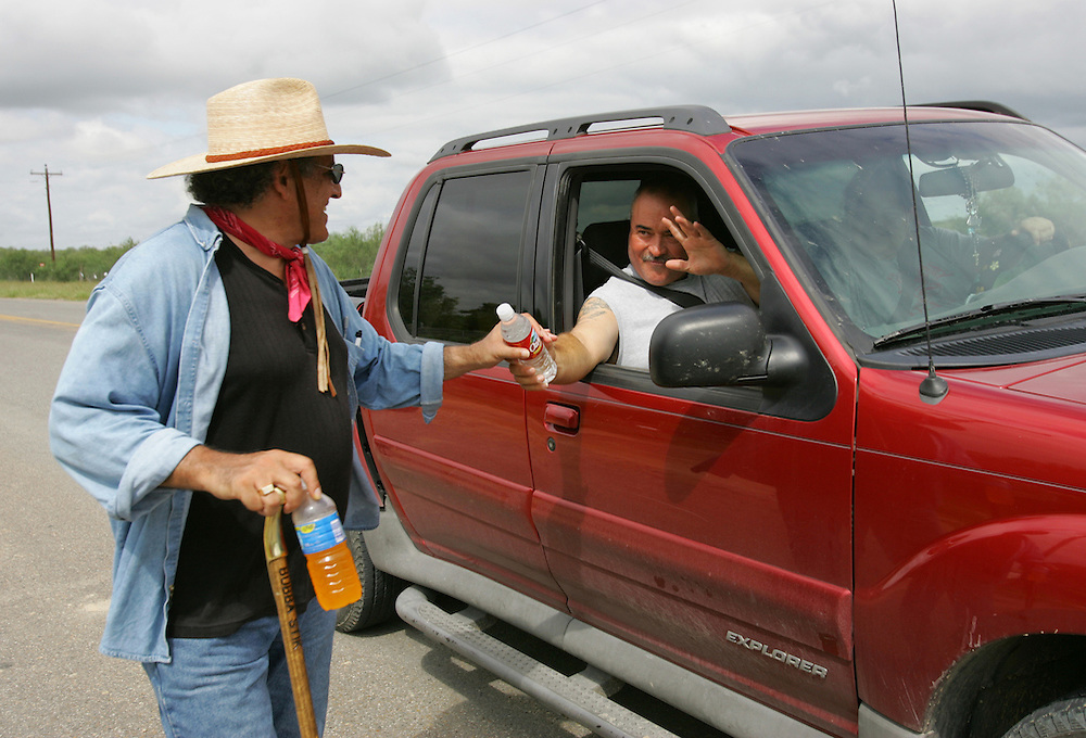 A passing motorist stops to offer Jay Johnson Castro a bottle of water as he walks outside of Roma, approximately halfway through his trip.