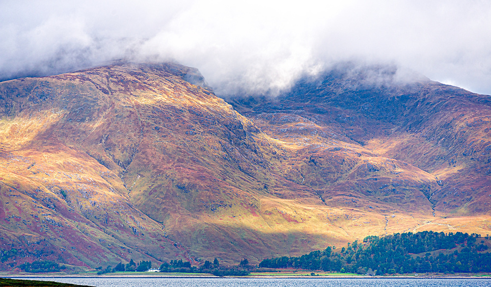 Iconic highland scene of massive mountainside uttely dwarfing what is a sizeable building. Clouds raking the hilltop, sun and shaddows racing over cascading burns of white water.
