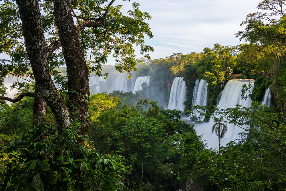 View of several waterfalls from the Upper Trail (Circuito Superior) on the Argentinian side of Iguazu Falls. On the far right a group of tourists enjoy the view.