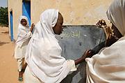 Displaced people at Dar El Salam School in Krindig Two camp. Two young girls write on a blackboard. El Geneina, Darfur, Sudan.