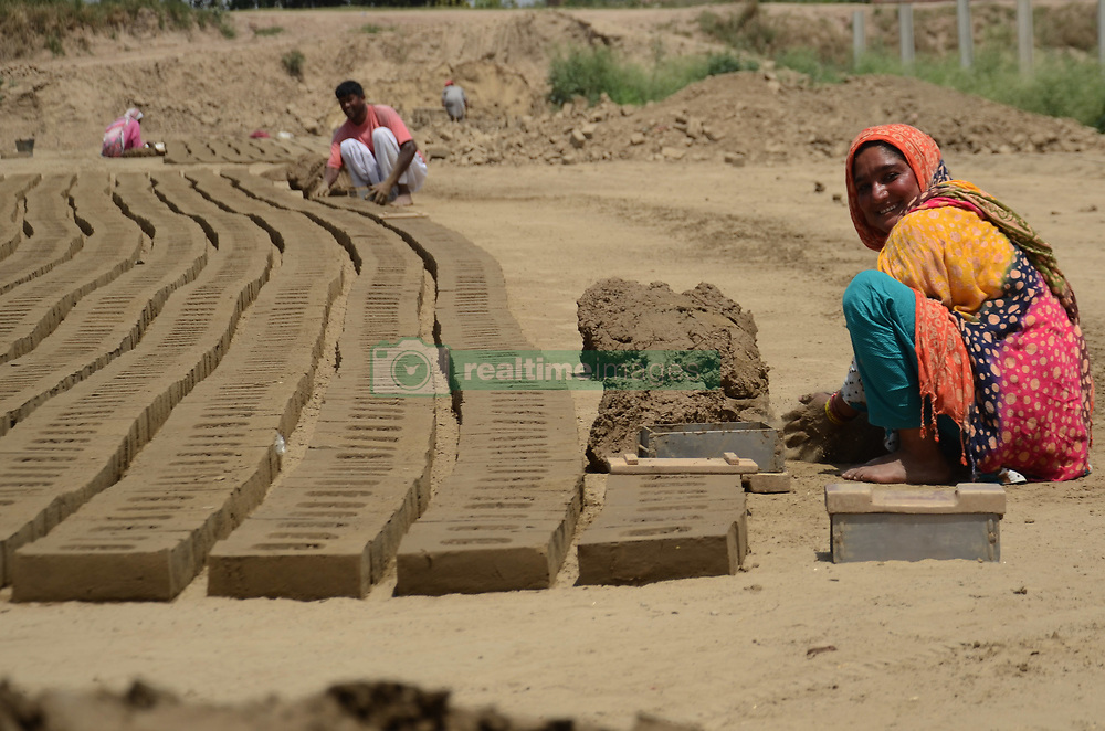 """April 30, 2019 - Lahore, Punjab, Pakistan - Pakistani villagers women and family members laborers are busy in preparing of clay tiles at a bricks klin on the eve of International Labour Day Lahore . May 1st, International Workers Day, commemorates the historic struggle of working people throughout the world. The 1904 International Socialist Conference in Amsterdam, the Sixth Conference of the Second International, called on All Social Democratic Party Organizations and Trade Unions of All Countries to demonstrate energetically on the first of May for the legal establishment of the 8-hour day, for the class demands of the proletariat, and for universal. celebrates all over the global to pay tribute to those who laid down their lives in Chicago in 1886 for the rights of laborers with the theme of Uniting Workers for Social and Economic Advancement. It was in 1972 when Pakistan,s first labor policy was devised and May 1st was officially declared as a holiday. Pakistan,s labor constitutes without doubt the most miserable community in the country. Labor Day is an annual holiday celebrated all over the world on May 01"""" that resulted from efforts of the labor union movement, to celebrate the economic and social achievements of workers. The holiday was organized by the Central Labor Union to exhibit ''the strength and esprit de corps of the trade and labor. International Workers' Day, also known as Labor Day or Workers' Day in some countries and often referred to as May Day, is a celebration of laborers and the working classes that is promoted by the international labor movement which occurs every year on May Day  (Credit Image: © Rana Sajid Hussain/Pacific Press via ZUMA Wire)"""