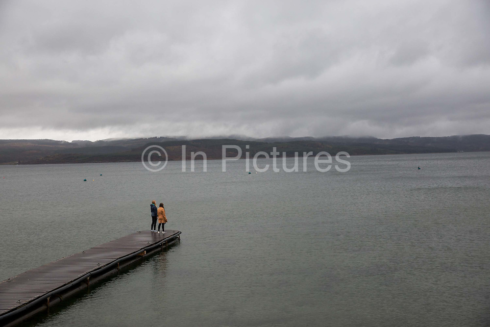 A female couple on a wooden pier overlooking Loch Fyne in Otter Ferry on the 3rd November 2018 on the Cowal peninsula in Argyll and Bute in Scotland in the United Kingdom.