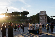 A man stands smoking a cigarette outside the Colosseum in Rome as he waits for customers for his souvenir stand.