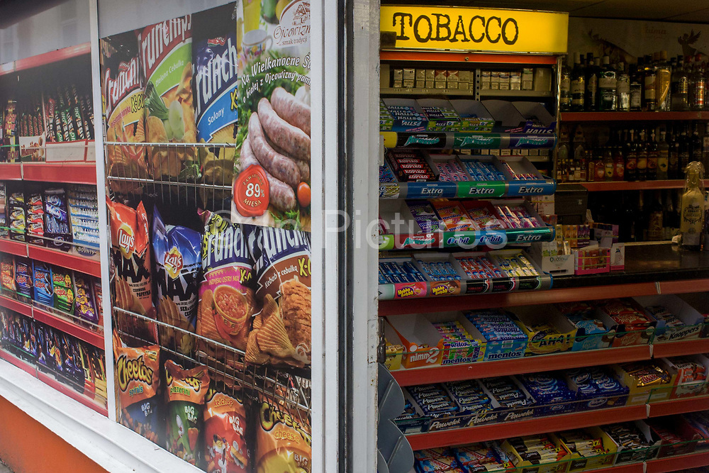 Frontage poster and shelves with stock of a corner shop in Weston-super-Mare. In a scene of confusing scale and perspective, we see both the real produce of sweets and confectionary inside the shop, under a Tobacco sign - and the oversized illustration of crisps and chocolate bars on the exterior of the business.