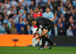 MANCHESTER, ENGLAND - Monday, April 30, 2012: Referee Mark Clattenburg picks up a plastic bag that has blown onto the pitch during the Premiership match between Manchester City and Manchester United at the City of Manchester Stadium. (Pic by Chris Brunskill/Propaganda)
