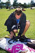 Fernando unpacks his kite and prepares to air it up.  Kites are held stiff by air pressure.