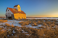 I found this old barn on the side of a road outside of Lincoln, IL. The foundation is fractured and the entire front end is sinking into the ground. The late evening sunlight was painting the barn gold as it melted what's left of the snow. It probably won't be long before it collapses and turns into a pile of rubble.<br />
