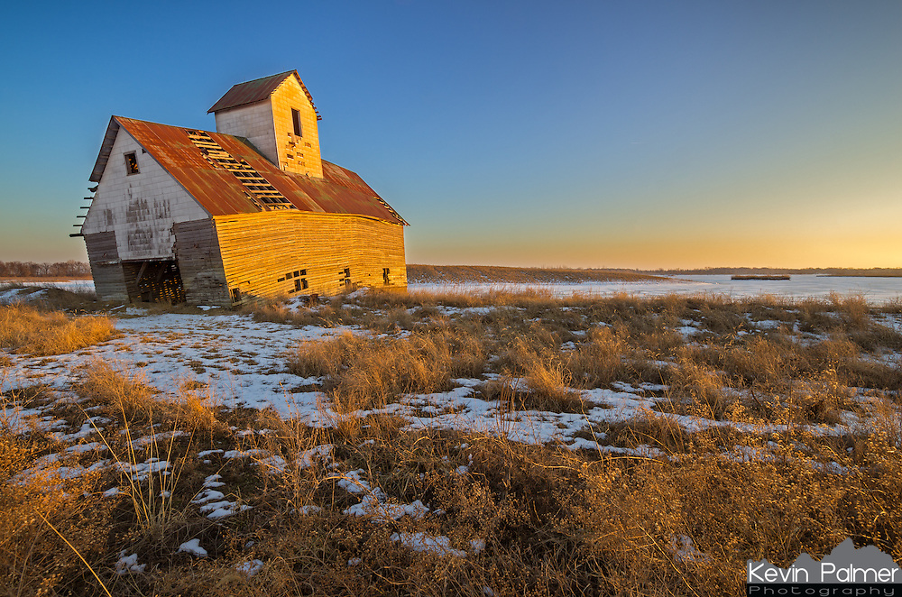 I found this old barn on the side of a road outside of Lincoln, IL. The foundation is fractured and the entire front end is sinking into the ground. The late evening sunlight was painting the barn gold as it melted what's left of the snow. It probably won't be long before it collapses and turns into a pile of rubble.<br /> <br /> Date Taken: February 6, 2015