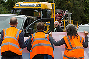 A motorist looks at Insulate Britain climate activists blocking a slip road from the M25, causing long tailbacks on the motorway, as part of a new campaign intended to push the UK government to make significant legislative change to start lowering emissions on 13th September 2021 in Godstone, United Kingdom. The activists, who wrote to Prime Minister Boris Johnson on 13th August, are demanding that the government immediately promises both to fully fund and ensure the insulation of all social housing in Britain by 2025 and to produce within four months a legally binding national plan to fully fund and ensure the full low-energy and low-carbon whole-house retrofit, with no externalised costs, of all homes in Britain by 2030 as part of a just transition to full decarbonisation of all parts of society and the economy.