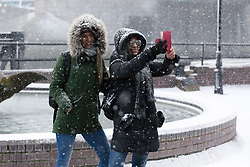 © Licensed to London News Pictures. 27/02/2018. London, UK. Two tourists take a selfie during a heavy snow shower near Tower Bridge in London this afternoon. Following the snow shower, the capital saw bright sunshine and clear sky. Photo credit: Vickie Flores/LNP