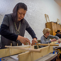 Elaine Bowman threads a loom during a weaving class at Weaving in Beauty in Gallup Saturday.