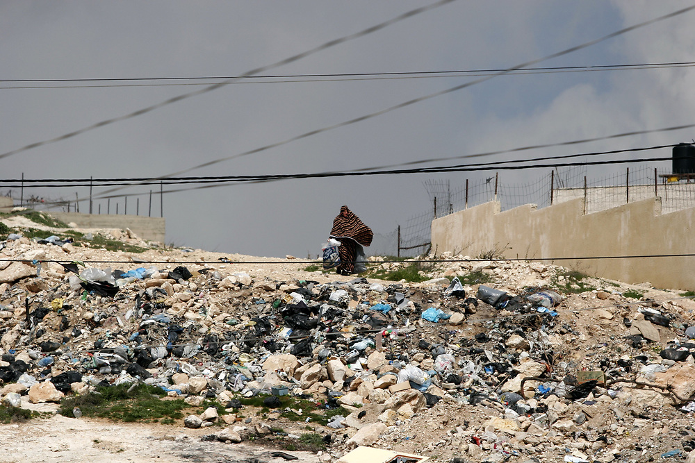 A Palestinian woman walks past a pile of garbage on her way home after clashes between Palestinians and Israeli border police erupted in the West Bank refugee camp of Shuafat, in East Jerusalem, on March 3, 2008. Clashes broke out across the West Bank on Monday between Israeli troops and Palestinian youths protesting Israel's Gaza operations.