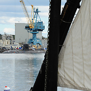 A crane and nuclear submarine at the Portsmouth Naval Shipyard provide  an interesting backdrop for the Gundalow's slightly older technology