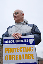 Man holding a banner on an official PCS picket,