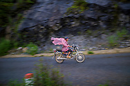 A vietnamese man rides a motorbike by a rainy day on the road between Bac Ha and Coc Pai (Xin Man), Vietnam, Southeast Asia