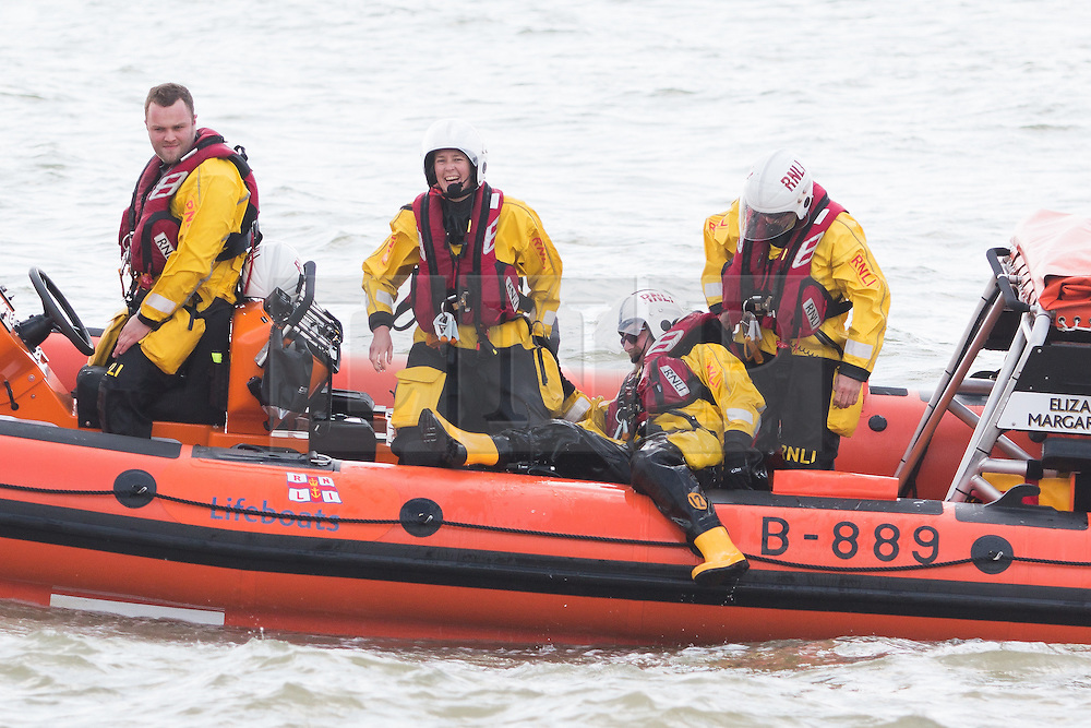 © Licensed to London News Pictures. 15/05/2016. Brighton, UK. Members of the Brighton RNLI lifeboat crew laugh as a colleague climbs aboard after delivering ice creams for his colleagues who are patrolling the sea off Brighton. Photo credit: Hugo Michiels/LNP