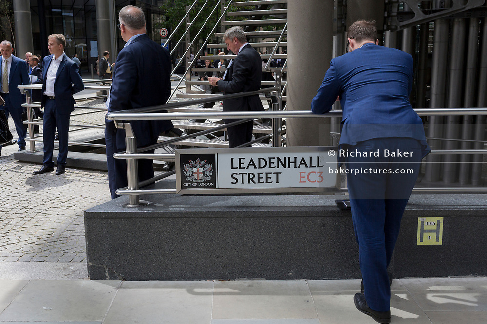 Insurance industry business people gather outside the Lloyds of London building on leadenhall Street in the City of London, the capital's financial district (aka the Square Mile), on 10th July 2019, in London England.