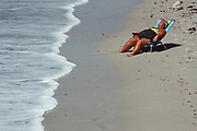 Basking in the Florida sunshine.. a woman lounges is her chair near the water taking in the sunshine while at the beach.