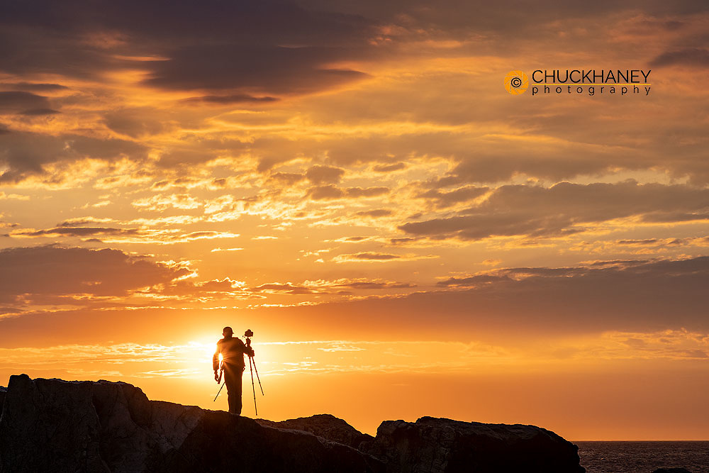 Photographer silhouetted at sunrise in Portland, Maine, USA