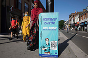 Members of the public pass a London Borough of Hounslow Covid-19 public information sign urging residents to take precautions to minimise the spread of the coronavirus amid rising concern regarding the Delta variant on 17th July 2021 in Hounslow, United Kingdom. The UK government is currently still expected to lift almost all restrictions on social contact on 19th July, known as Freedom Day, but the current wave driven by the Delta variant is not expected to peak until mid-August.