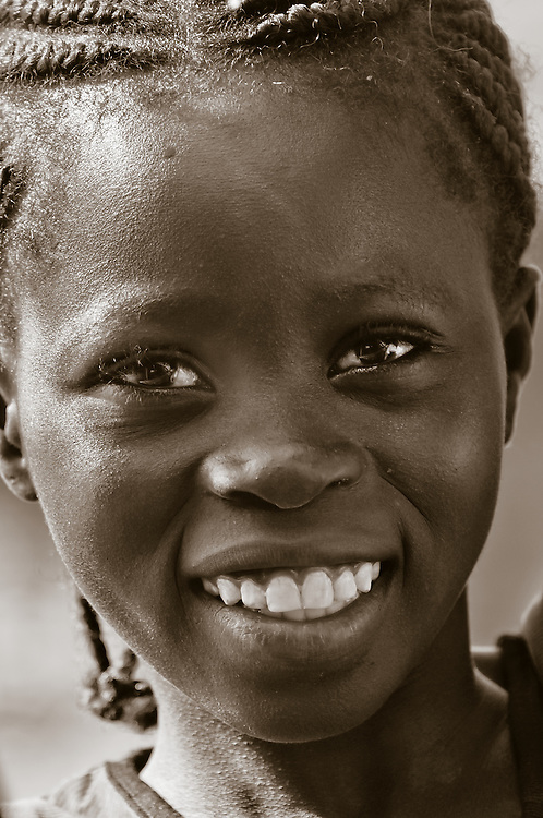 Portrait of a young Burkinabe girl selling fruit on the road to the Sahel