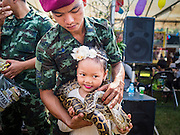 """14 JANUARY 2017 - BANGKOK, THAILAND: A Thai soldier puts a python around a child's neck during Children's Day activities at the King's Guard, 2nd Cavalry Division base in Bangkok. Thailand National Children's Day is celebrated on the second Saturday in January. Known as """"Wan Dek"""" in Thailand, Children's Day is celebrated to give children the opportunity to have fun and to create awareness about their significant role towards the development of the country. Many government offices open to tours and military bases hold special children's day events. It was established as a holiday in 1955.        PHOTO BY JACK KURTZ"""