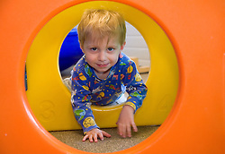 United States, Washington, Bellevue, boy crawling through hole in play structure at Kindering Center